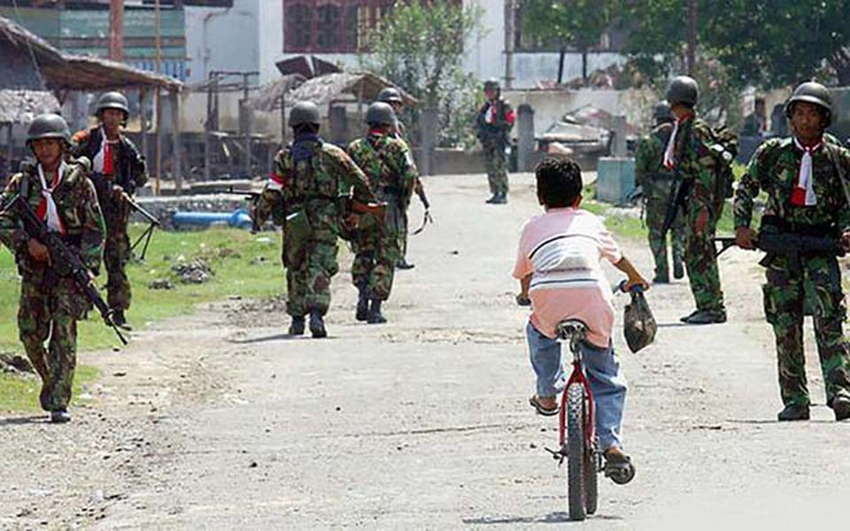 Child rides bike past Indonesian soldiers in Aceh (Tirto)