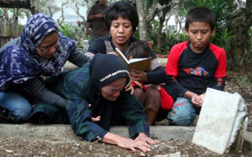 Suciwati with her two children and family members at Munir's grave (Tempo)