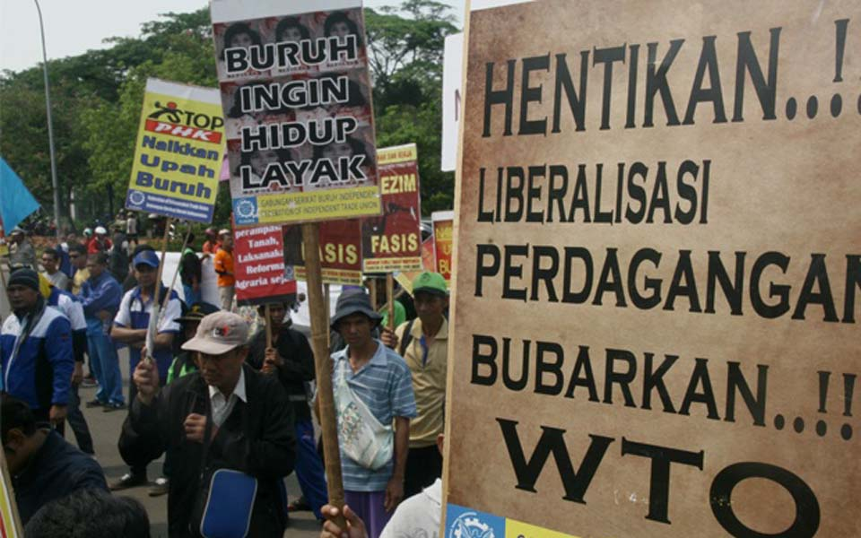 Banner reads 'End Trade Liberalisation Disband the WTO' (Satu Harapan)