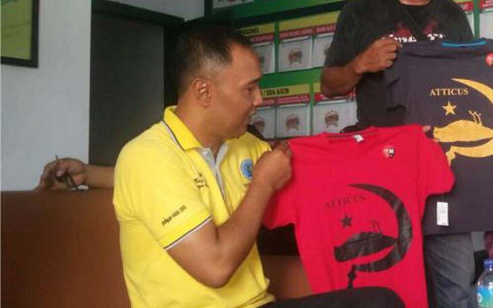 Plain clothed police officers display confiscated hammer-and-sickle T-shirts (Berita Jatim)