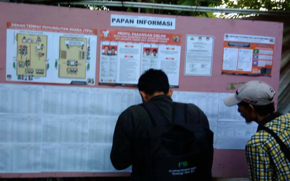 People check for their names on voter registration list in Jakarta (Arah)