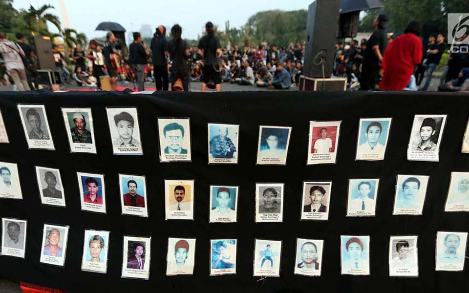 Activists display photos of victims of rights violations during Thursday action at State Palace (Liputan 6)