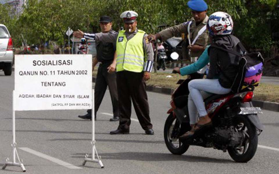 Police checkpoint stops woman riding on motorbike in Lhokseumawe - January 4, 2013 (Kompasiana)