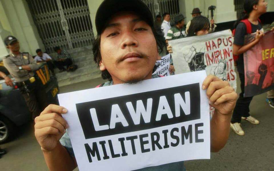 Protester holds banner reading 'Fight Militarism' in Bandung - May 26, 2017 (Buli Ju)