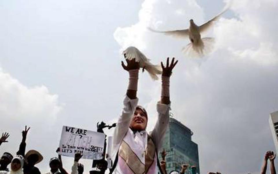Protester releases doves at rally for peace in Aceh (elsam)