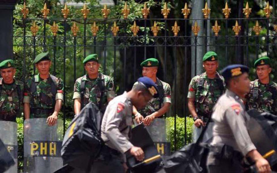 Brimob officers walk past TNI soldiers (simomot)