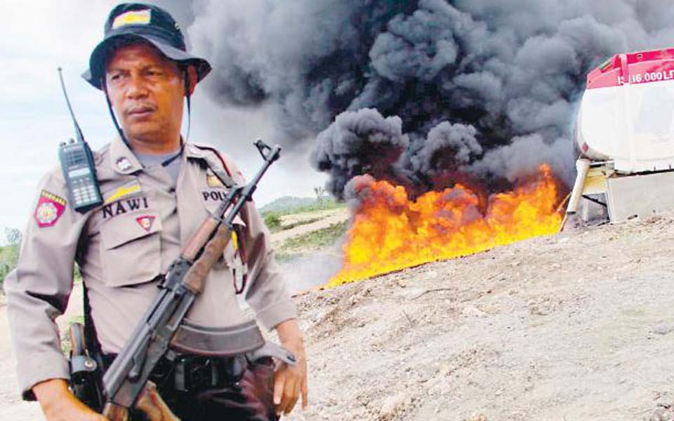 Indonesian police officer stands in front of oil fire in Aceh (Tribune)