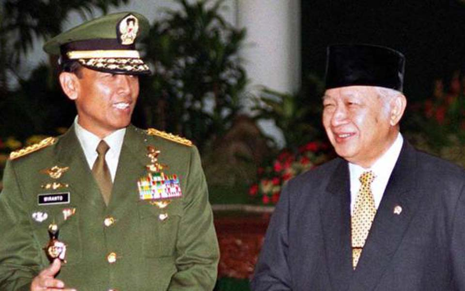Try Sutrisno pictured left with former president Suharto (Merdeka)