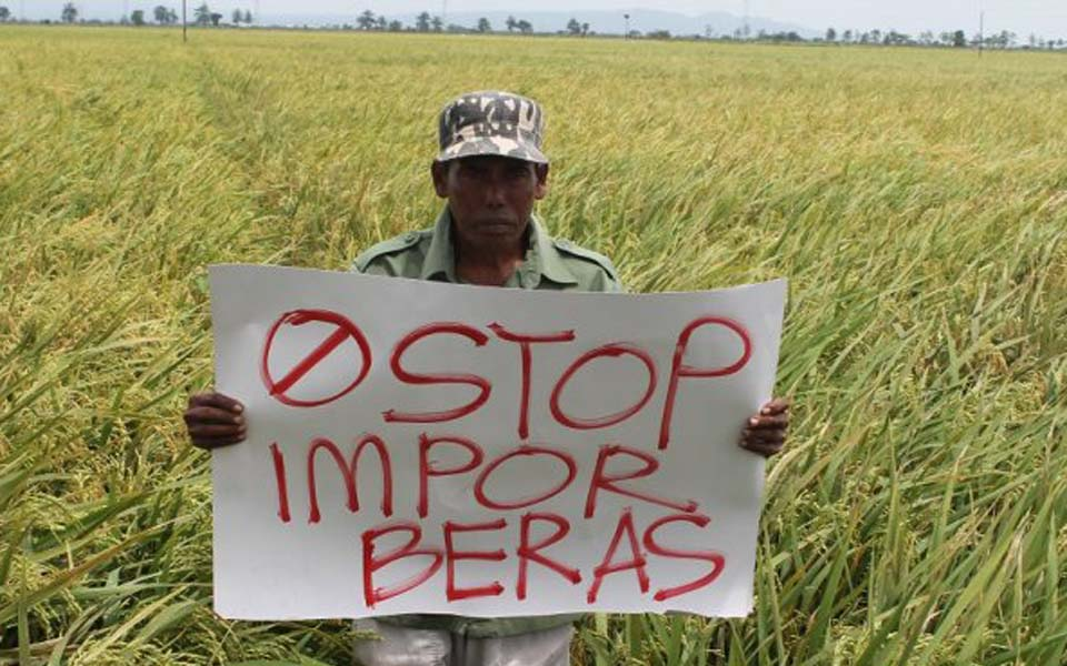 Banner reads 'Stop rice imports' (Tribune)