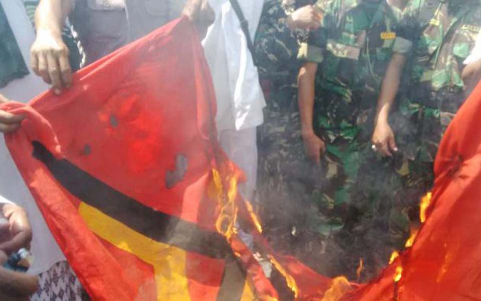 Soldiers watch as Islamic Defenders Front burn communist flag (Kompas)