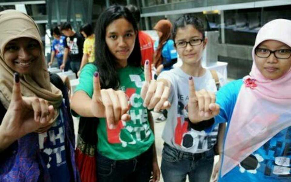 Young women show ink stained fingers after voting (tengokberita)