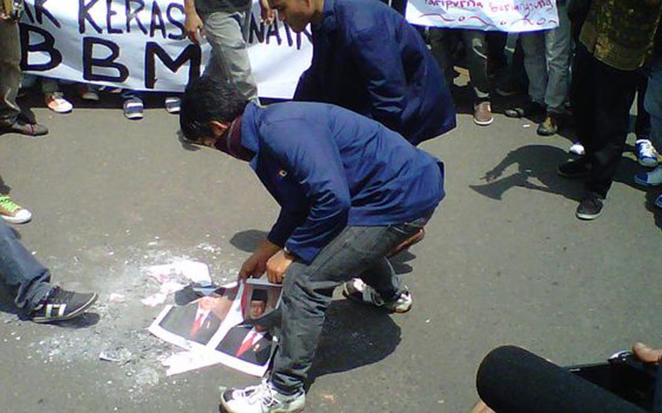 Protester tramples on burnt pictures of SBY and Boediono (Tribune)
