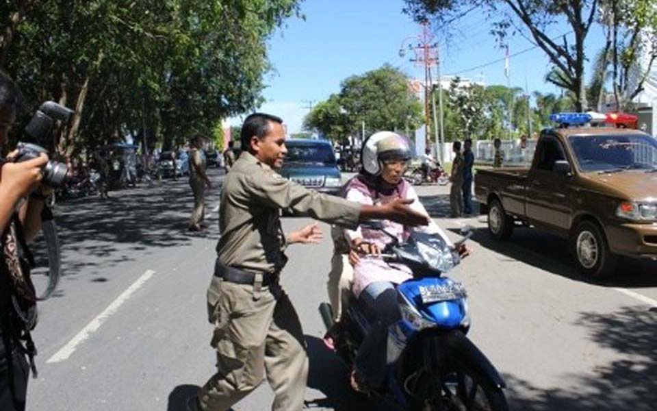 Official pulls over  woman riding on motorbike in Lhokseumawe - April 13 2013 (Detik)