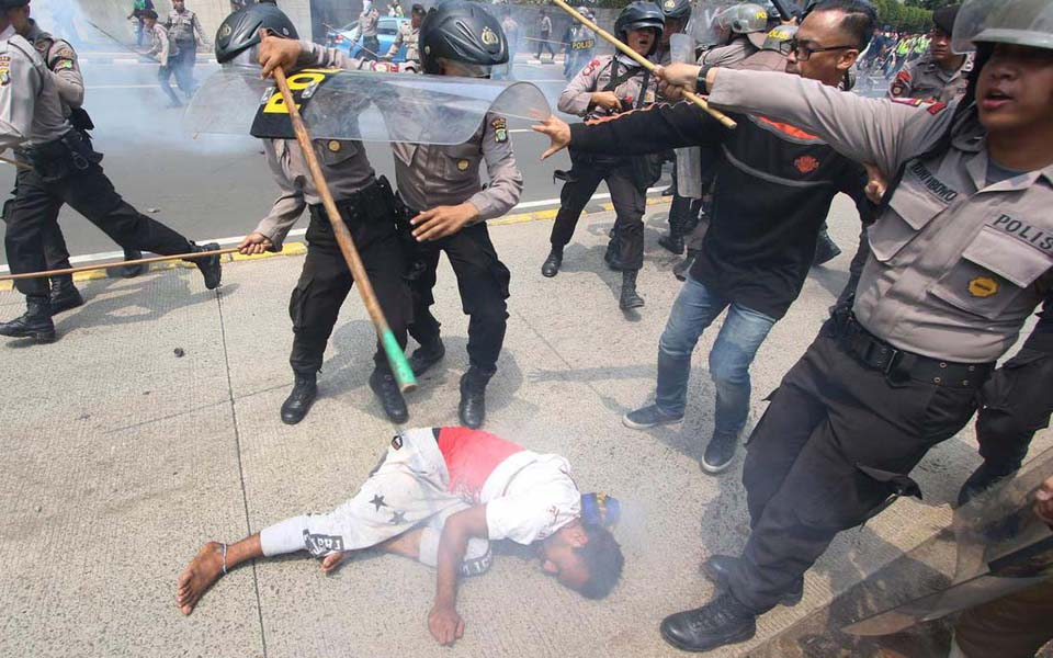 AMP protester being beaten police near Hotel Indonesia traffic circle in Jakarta - December 1, 2015 (Liputan6)