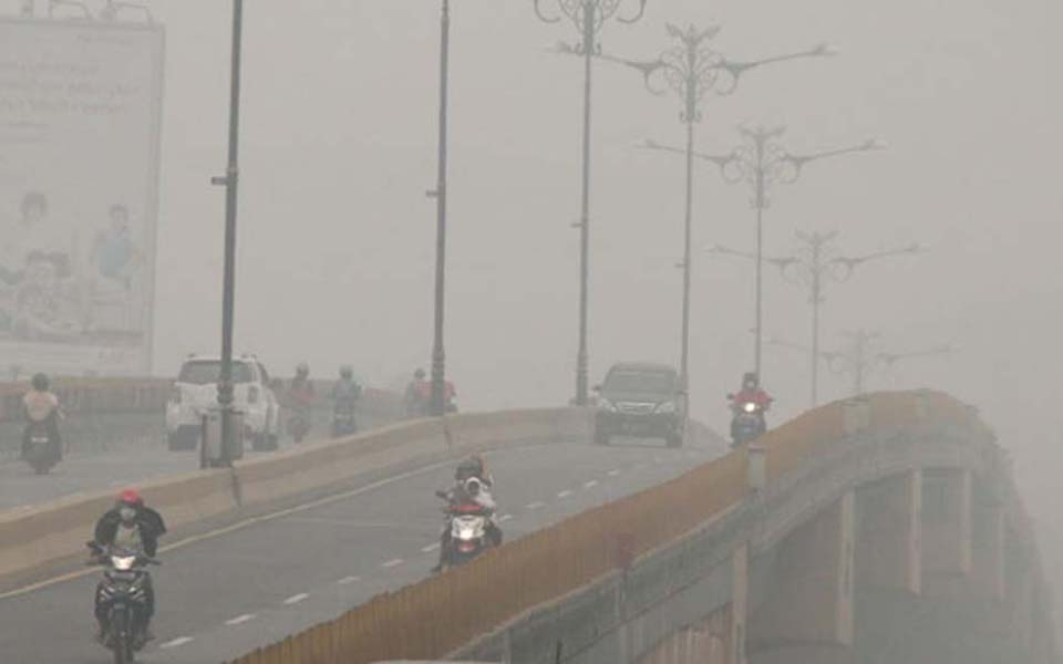 Driver cross bridge covered in haze from forest fires in Pekanbaru, Riau - September 30, 2015 (Antara)