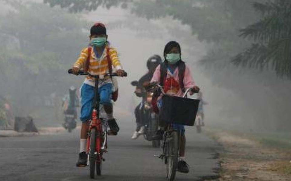 School children ride through haze from forest fires - Undated (kemkes)