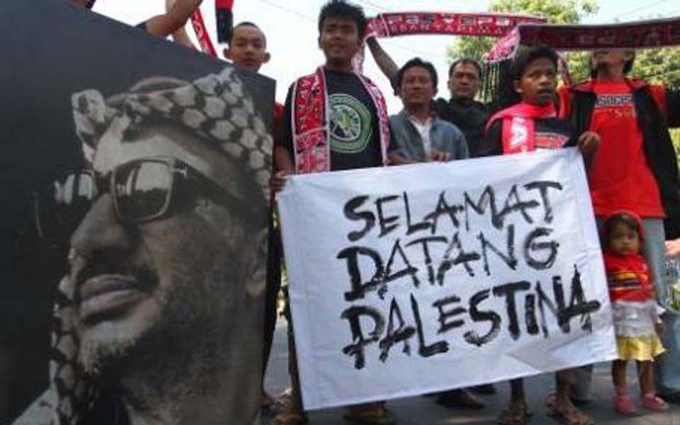 Indonesian sports fans support Palestine by holding picture of Yaser Arafat