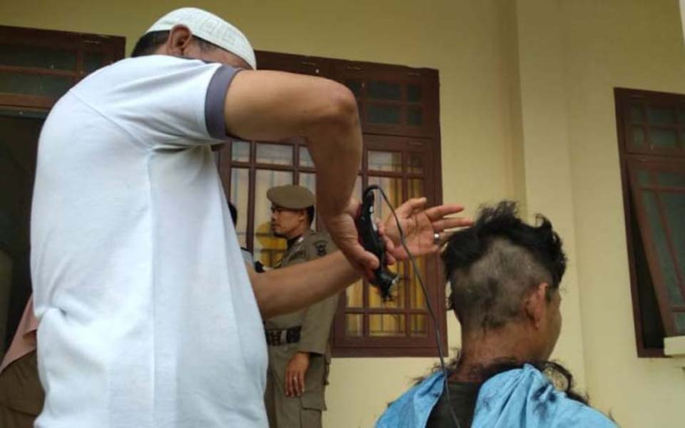 Religious police shaving the head of a transgender women (Kumparan)