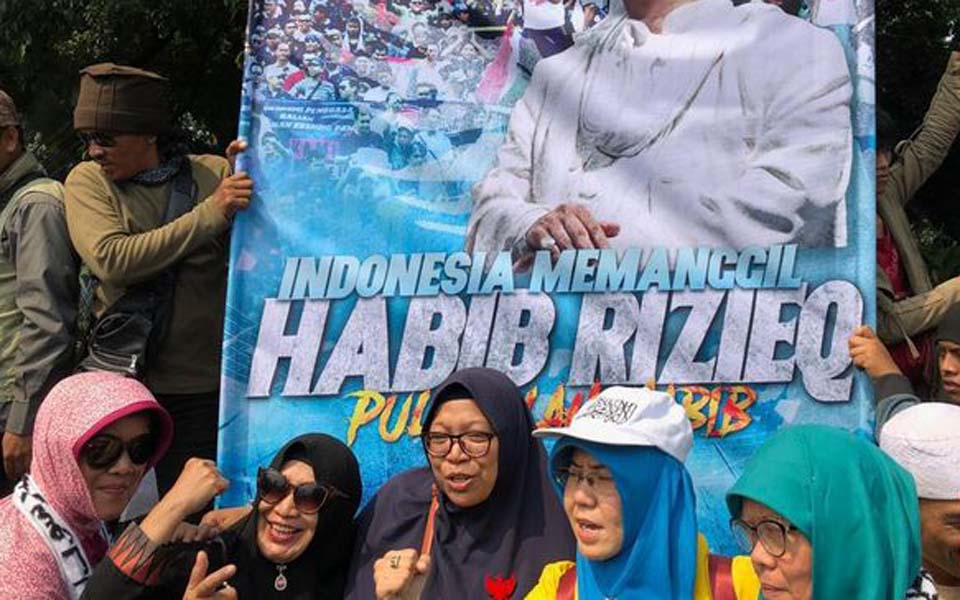 Fans pose for selfies in front of Rizieq Shihab banner – June 26, 2019 (CNN)