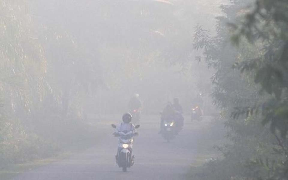 Motorists drive through haze from forest fires (Antara)