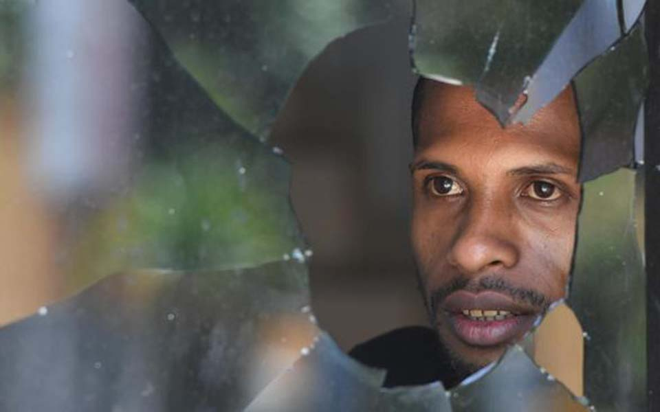 Papuan man looks through broken window in Jayapura – August 31, 2019 (Antara)