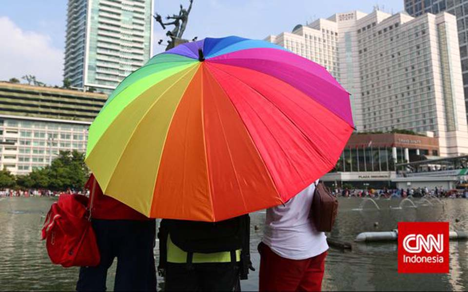 People hold rainbow umbrella at Hotel Indonesia traffic circle – Undated (CNN)